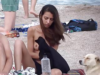 Lovely Young Woman Sunbathing On Public Beach
